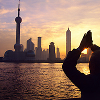 Old man performing morning exercises on the Bund, facing towards the rising sun and the new skyscrapers of Pudong District, including the 457 metre high Oriental Pearl TV Tower.<br /> <br /> From China [sur]real &not;&copy; Mark Henley