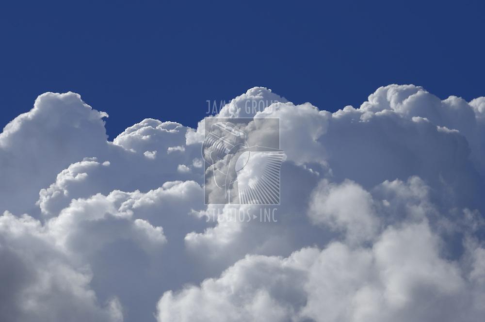 Cumulus clouds shot from a high altitude against a dark blue sky