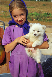 Young amish girl with pet puppy dog at road side food stand, Lancaster County, PA.