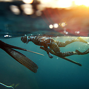 "SUMMARY - ""Blood in the Water"" Spearfishing is a type of hunting done with underwater guns, harpoons and strong line. Freediving is a type of breath-hold diving in which divers descend for the duration of one breath, without any SCUBA tanks or any breathing apparatus. The best freedivers can hold their breath for over five minutes and go deeper than 100 feet. The combination of both these skills makes a high adrenaline sport done by only a few brave souls...THIS IMAGE - Ren Chapman prepares for a dive with a loaded and ready speargun while another diver rests, holding onto a dive-line to stay in position against the current.  ""Blood in the water - Predive"""
