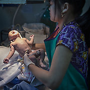 Ethnic Karen medics help a young Karen refugee mother with birth at a makeshift neonatal clinic inside the Mae Hla refugee camp along the Thai-Burma Border.