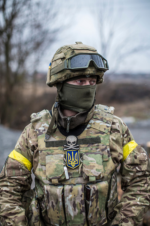 SARTANA, UKRAINE - FEBRUARY 5, 2015: A member of the St. Mary's Battalion, a pro-Ukraine militia,  guards a checkpoint in Sartana, Ukraine. With more than 220 people having died in the past several weeks, a new diplomatic push is underway to bring an end to fighting between pro-Russia rebels and Ukrainian forces. CREDIT: Brendan Hoffman for The New York Times