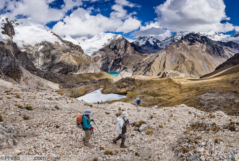Hikers descend from Caracara Pass into Alpamayo Valley in Huascaran National Park (UNESCO World Heritage Site), Cordillera Blanca, Andes Mountains, Peru, South America. Above left of turquoise Jancarurish Lake is the pyramidal peak of Nevado Alpamayo (19,511 ft or 5947 m). This is day 6 of 10 days trekking around Alpamayo (starting from Vaqueria). This panorama was stitched from 4 overlapping photos.