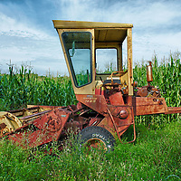 Abandoned crop harvester in a cornfield in Litchfield County, Connecticut.  HDR photo taken in August, as the corn in the field behind is ready to be picked.