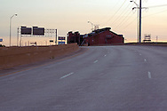Looking west into the sun, one of the many processing buildings of the ArcelorMittal steel mill peaks above the elevated structure of the abandoned Cline Avenue.
