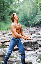 shirtless man in a river tossing water into the air with a pan