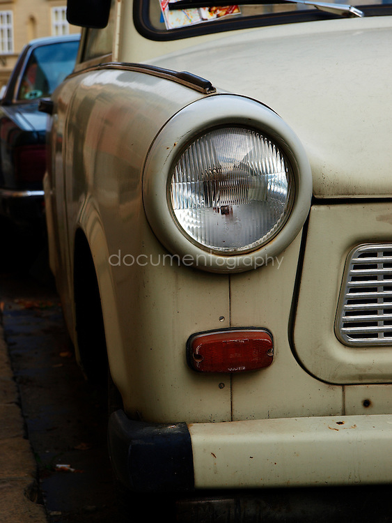"Close-up detail of a trabant. The name Trabant means ""fellow traveler"" (Satellite) in Latin; the name was inspired by Soviet Sputnik. The cars are often referred to as the Trabbi or Trabi, pronounced with a short a. It was the most common vehicle in East Germany, and was also exported to countries both inside and outside the communist bloc. The main selling points were that it had room for four adults and luggage, and was compact, light and durable. Despite its poor performance and smoky two-stroke engine, the car has come to be regarded with affection as a symbol of the more positive sides of former East Germany and of the fall of communism, Budapest, Hungary."