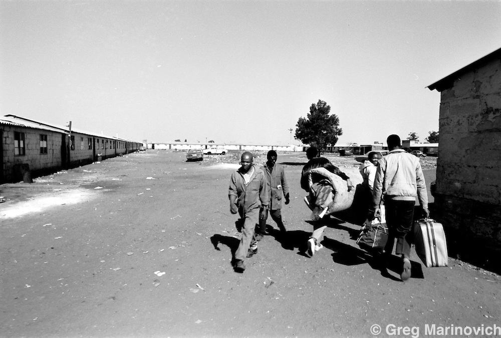 Hostel residents leave during a lull in the fighting August 17, 2003 at the ....hostel in Tokoza on the East Rand some 20km East of Johannesburg. The migrant workers' hostel was later destroyed in the clashes between Inkatha Freedom Party supporters and those of the African National Congress. (Photo by Greg Marinovich)