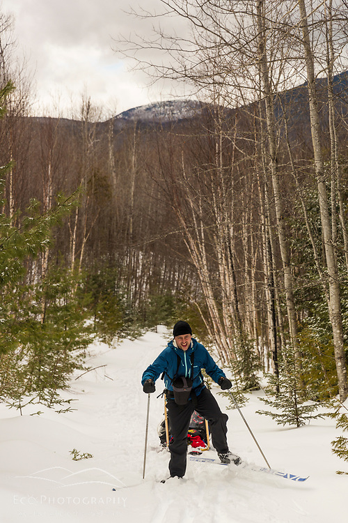 A skier tows a sled uphill in the backcountry of Maine's Katahdin Woods and Waters National Monument.