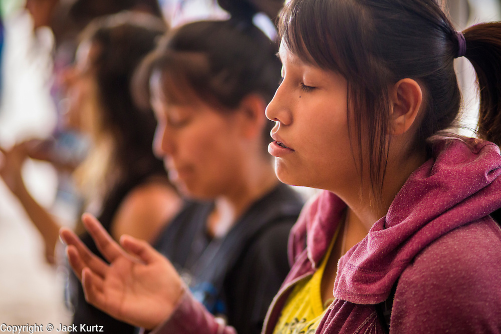 """12 JULY 2012 - FT DEFIANCE, AZ: Navajo teenagers pray during the youth worship at the 23rd annual Navajo Nation Camp Meeting in Ft. Defiance, north of Window Rock, AZ, on the Navajo reservation. Preachers from across the Navajo Nation, and the western US, come to Navajo Nation Camp Meeting to preach an evangelical form of Christianity. Evangelical Christians make up a growing part of the reservation - there are now more than a hundred camp meetings and tent revivals on the reservation every year. The camp meeting in Ft. Defiance draws nearly 200 people each night of its six day run. Many of the attendees convert to evangelical Christianity from traditional Navajo beliefs, Catholicism or Mormonism. """"Camp meetings"""" are a form of Protestant Christian religious services originating in Britain and once common in rural parts of the United States. People would travel a great distance to a particular site to camp out, listen to itinerant preachers, and pray. This suited the rural life, before cars and highways were common, because rural areas often lacked traditional churches.      PHOTO BY JACK KURTZ"""