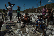 RENDEL, HAITI - OCTOBER 12, 2016: A woman takes journalists to  to show where she collects drinking water from the river that runs along the village of Rendel, and is believe to be contaminated and spreading Cholera. A week has passed since Hurricane Matthew tore through this remote stretch of Haiti's southern peninsula, leaving an apocalyptic landscape of treeless countryside, disarticulated homes and a land stripped of its natural riches.  But for many, the torment has only started.  What began as a small cholera outbreak in the mountains before the hurricane has now spread into every crevice of this valley and the hills above. First came the sick, who trudged down to Rendel in search of medical care, bringing the disease with them. Then, when the floods came, cholera was carried down by the water itself, which swept up fecal matter dumped on the hillsides, contaminating the river and other drinking supplies.  Water unboiled or unchlorinated and poor hygiene meant the infections spread rapidly.  PHOTO: Meridith Kohut for The New York Times