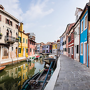 """In Burano, houses are brightly painted blue, red, orange, and yellow along a fishermen's boat canal. Burano, known for knitted lacework, fishing, and colorfully painted houses, is a small archipelago of four islands linked by bridges in the Venetian Lagoon, in the Veneto region of Italy, Europe. Burano's traditional house colors are strictly regulated by government. The Romans may have been first to settle Burano. Romantic Venice (Venezia), """"City of Canals,"""" stretches across 100+ small islands in the marshy Venetian Lagoon along the Adriatic Sea in northeast Italy, between the mouths of the Po and Piave Rivers. Venice and the Venetian Lagoon are honored on UNESCO's World Heritage List. This panorama was stitched from 6 overlapping photos."""