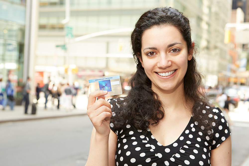 Lifestyle image of smiling Middle Eastern girl with American Express AMEX credit card