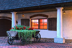 Old cart with flowers at wall of old building in Vastseliina, Estonia. Lighted window.
