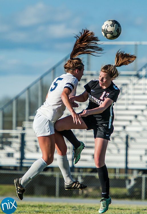 Hickory Ridge's Anna Keightley (5) and Jay M. Robinson's Marie Spokas (13) go up for a header Friday night at Hickory Ridge High School in Harrisburg. The game ended in a 2-2 draw after double overtime.