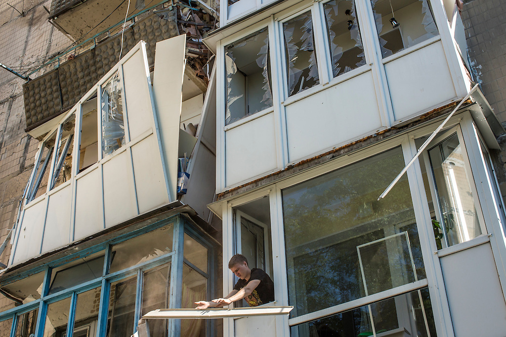 A man tosses a broken window frame from his apartment after the building was hit by a supsected grad rocket strike on Tuesday, July 29, 2014 in Donetsk, Ukraine.