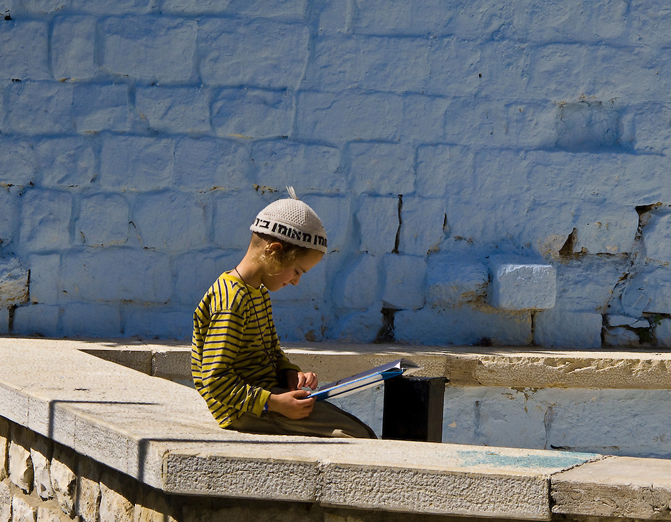 An orthodox Jewish child reads a book. Zefat, Israel.