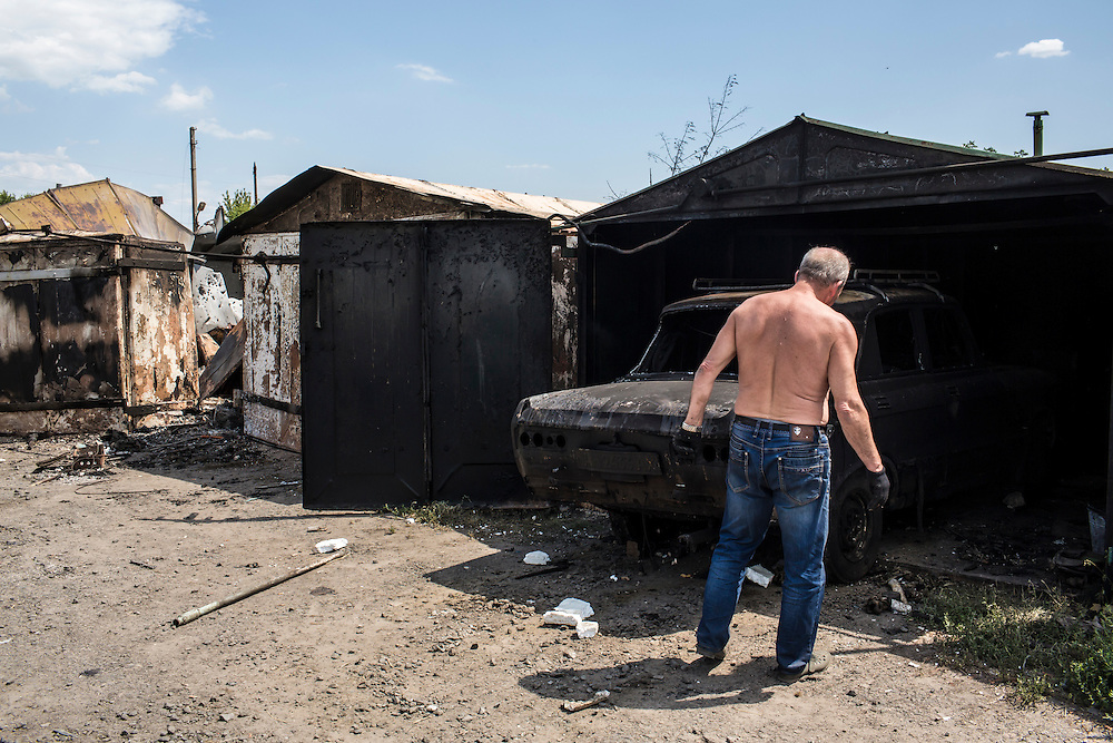 A resident of the Ploshchadka neighborhood, which has been heavily bombarded in recent days, moves a burned car after a nearby garage was hit by a grad rocket on Wednesday, July 30, 2014 in Donetsk, Ukraine.