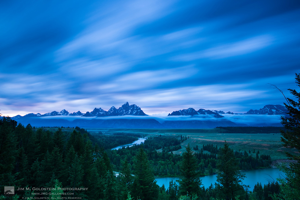 Clouds illuminate with red light above the Grand Teton mountains seen from the Snake River lookout at sunset - Grand Teton National Park, Wyoming