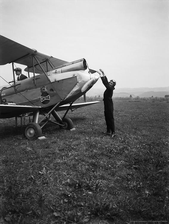 Lores Bonney, Australian pioneering aviatrix starting her plane, a De Havilland Gypsy Moth, 1933