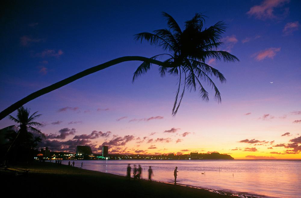 Twilight at Tumon Bay resort area with palm tree over beach; Guam, Micronesia.