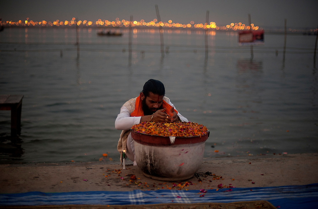 A Hindu devotee lights a candle on the banks of the holy river on February 9, 2013 in Allahabad, India during the Kumbh Mela. — © Jeremy Lock/