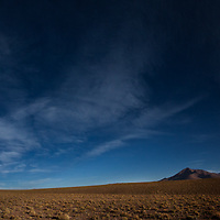 An empty small road in a wide panoramic landscape in the Eduardo Avaroa Andean Fauna National Reserve in Southwest Bolivia.