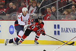 Jan 25, 2013; Newark, NJ, USA; New Jersey Devils left wing Mattias Tedenby (21) skates with the puck while being defended by Washington Capitals left wing Jason Chimera (25) during the first period at the Prudential Center.