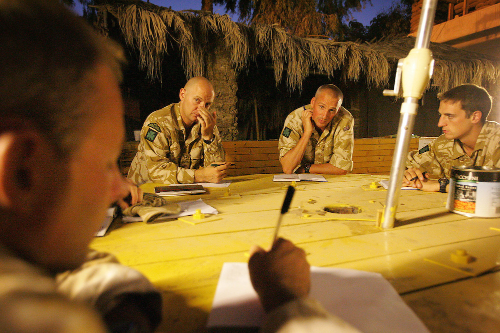 Baghdad, Iraq, 2 Oct 2005. Running 'Route Irish'...L-R Major Colin Wier, SGT Spence, SGT Fell and 2LT Campbell azt evening briefing.....B Company, 1st Battalion, The Royal Irish Regiment, a tight-knit multi national fighting force make daily escorting runs along ?Route Irish?, the infamous Baghdad Airport road. The 46 man team are all British Army regulars but come from as far afield as Fiji, South Africa and Northern and Southern Ireland. Previous deployments in Kosovo, Sierra Leone and Northern Ireland have equipped them with the valuable skills needed to provide protection for British Forces and materials transiting the world?s most dangerous highway. Due to an increased presence of US forces along the route both in dug in positions and mobile patrols, attacks along the road have slackened, despite this a day rarely passed without an IED (improvised explosive device) being detonated or a small arms attack against coalition forces. ..The convoy attempts to maintain a seclusion ?bubble? around its vehicles for the duration of the journey. Any civilian vehicle that either strays into the bubble or refuses to keep their distance represents a threat and should they ignore the warning blasts on air horns carried in each vehicle the rules of engagement progress from warning shots to use of lethal force. The relative safety of the International Zone offers them an opportunity to decompress between missions. A duty driver ferries soldiers to the ?Liberty Pool?. Once only frequented by Iraq?s Ba?athist elite the luxury swimming pool and gym now fills with troops. Their body armour, helmets and weapons all within easy reach they either soak up the sun or compete with each other in diving competitions. After a daily briefing the troops have access to the ?Mosquito and Camel? bar where they watch TV or play pool and in accordance with the ?2 can rule? are allowed to drink 2 beers per night.