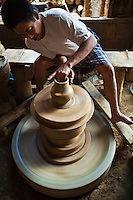 Filipino potter turning the pottery wheel manually - Burnay is a type of earthenware crafted by a potter's hands with the aid of a potter's wheel using sand for tempering and is fired at a high temperature in huge  kilns that makes it more durable than other terra cotta. It is said that the burnay technique was brought to Vigan by Chinese artisans.
