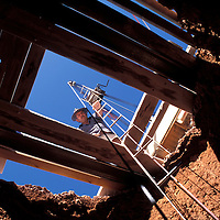 Australia, South Australia, (MR) Kary Aberhart hauls miner up 100' deep opal mine shaft in Coober Pedy.