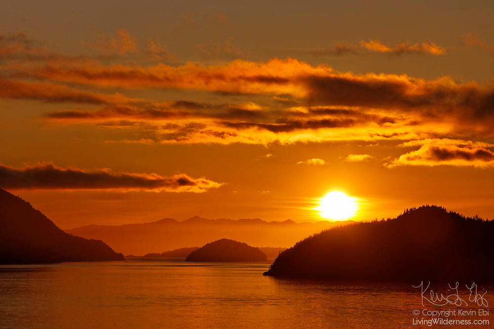 The sun sets over several islands in Howe Sound, located in British Columbia, Canada. In this view from Brunswick Point, Bowen Island is visible at left, Hutt Island is the small island in the center of the frame, and Gambier Island is visible at right. The mountains of Vancouver Island are visible in the background.