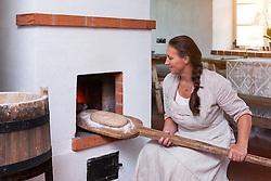 Woman at stove in Hellenurme watermill, Estonia. Preparing, bread on baker`s shovel. Rural interior.