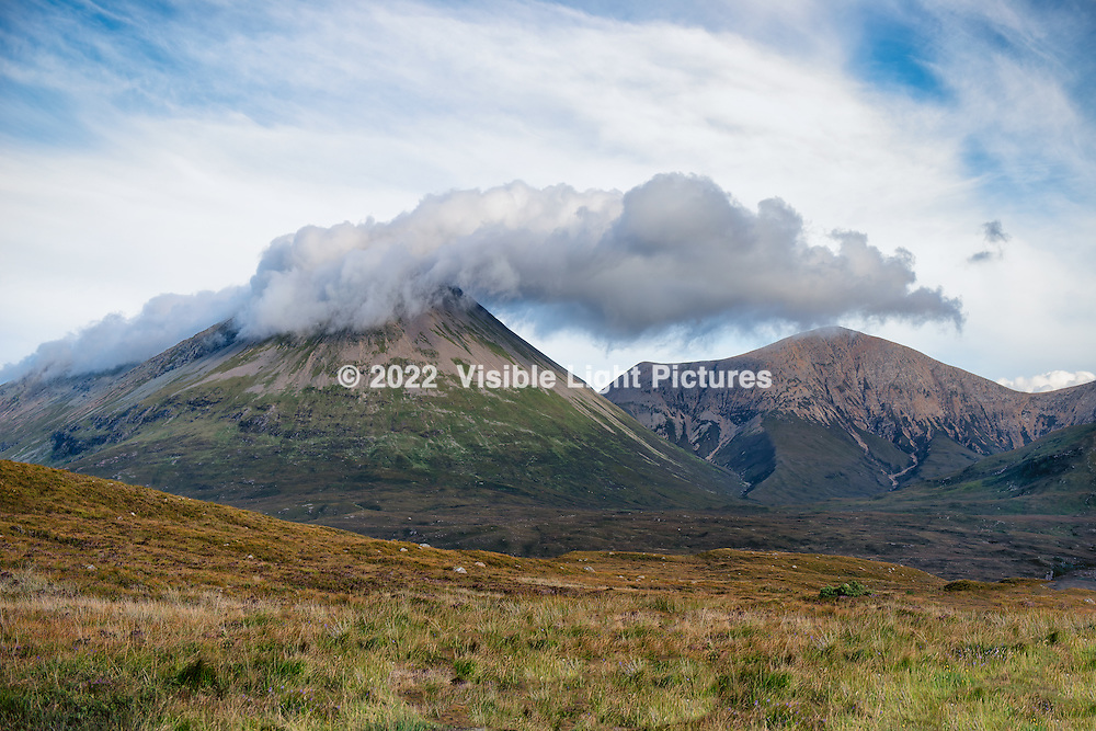 These are clouds occluding the peak of a mountain on the Isle of Skye in Scotland.  This is also known as orographic uplift, where moist air comes into contact with the mountainside, causing it to elevate from the ground toward cooler air at a higher altitude.  A darker cloud and rain showers often develop on the leeward side of the mountain, here on the right.