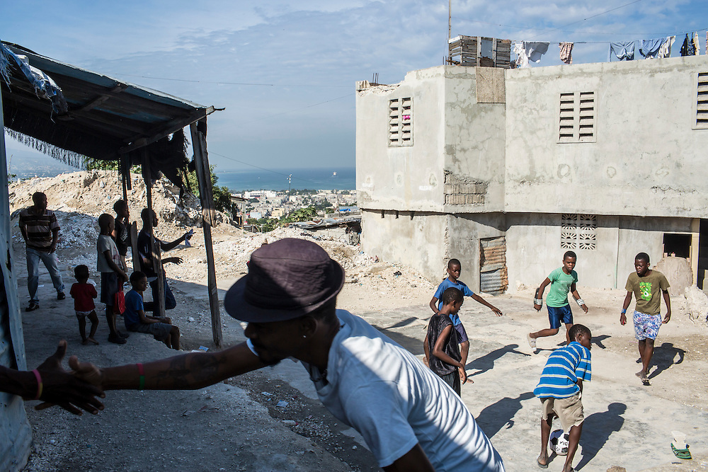 Kids play soccer as their coach greets friends in the Fort National neighborhood on Tuesday, December 16, 2014 in Port-au-Prince, Haiti. One of Port-au-Prince's poorer neighborhoods, Fort National was among the hardest hit by the 2010 earthquake. Still, its residents lack electricity or running water, and only several new homes have been built by the aid organizations and the government, despite years of promises.