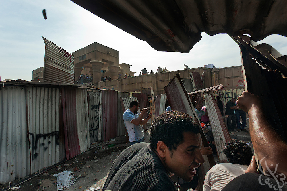 A mix of Salafi and revolutionary youth activists try to take cover behind makeshift shields as they battle Egyptian security forces, lobbing large stones and chunks of concrete during May 4, 2012 demonstrations against the ruling Supreme Council of the Armed Forces (SCAF) near the Defense ministry building in the Abbasiya district of Cairo. Close to 300 people were injured in the clashes, one killed, and an estimated 300 people arrested by the military.
