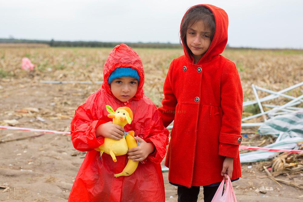 SERBIEN, Grenzstadt Berkasovo, Stadtgebiet von Šid. 08.10.2015 / Fluechtlinge an der serbisch-kroatischen Grenze: 2 Kinder warten auf den Grenzuebertritt, im eisigen Herbstwind. Die kroatische Grenze, und damit die EU-Aussengrenze, ist nur noch 100 Meter entfernt. Der Grenzuebertritt erfolgt zu Fuss und in Gruppen zu etwa 50 Personen.