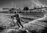 Village resident pushes his bicycle through wintertime fields constantly adjacent to the massive smokestacks of Baotou Steel plant, Baotou, Inner Mongolia, China.