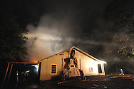 Oxford fireman work to extinguish a fire at a unoccupied house on South Lamar in Oxford, Miss. on Thursday, June 12, 2014. The fire was discovered by an Oxford Electric Department employee who was checking out a power outage at a next door residence.