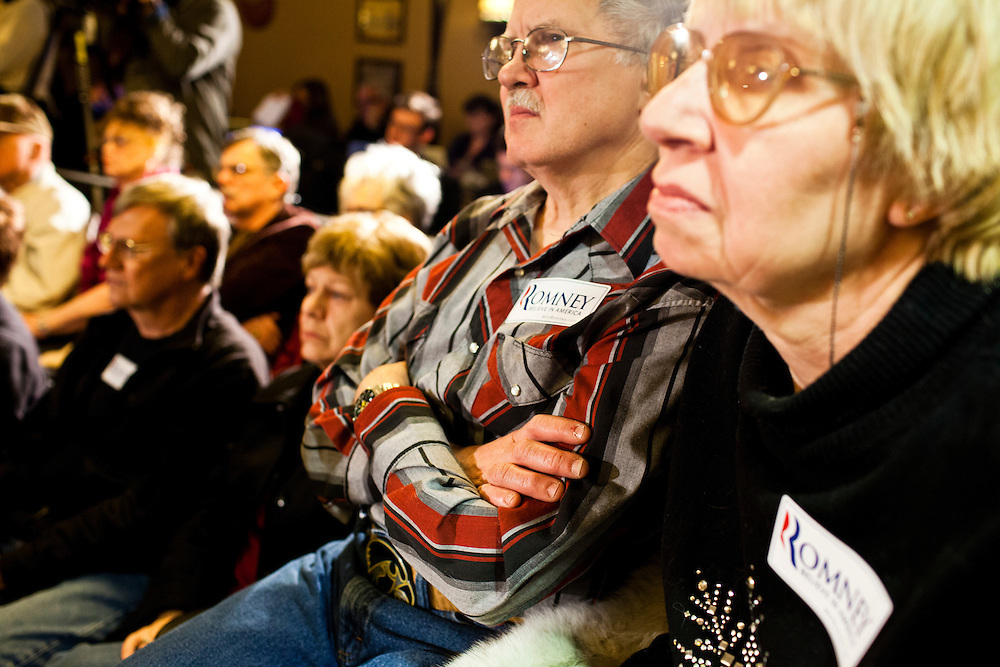 People listen as Republican presidential candidate Mitt Romney meets with voters at the Stoney Creek Inn on Saturday, December 31, 2011 in Sioux City, IA.