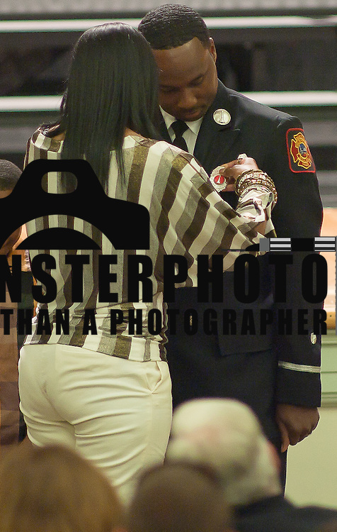 10/16/11 Wilmington DE: Lieutenant Demetrius A. Todd has his wife pin his badge on him during Wilmington Fire Academy promotion Ceremony Monday, Oct. 17, 2011 at P.S. Dupont Middle school in Wilmington Delaware...Funding for 13 of the 14 members of the current class is coming from a controversial grant approved by City Council this past spring...The 13 men and one woman make up the 36th Wilmington Fire Department Academy, which will bring the department up to 173 members...The News Journal/SAQUAN STIMPSON