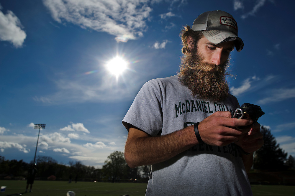photo by Matt Roth.Wednesday, April 11, 2012..Ron Shriver checks his iPhone after McDaniel College track practice in Westminster, Maryland Wednesday, April 11, 2012. .Ron Shriver is a retired marine staff sergeant. He is also the first in his family to attend college, thanks to the New G.I. Bill. His wife, a fellow retired Marine, is finishing up graduate school in Alaska. After Ron gets his undergraduate degree from McDaniel College in May, he plans to drive to Alaska with is two children Rory, 6, and Miles, 5. For the move Ron got rid of most of his family's belongings, and after his lease was up, he and his children moved back into his parent's farmhouse.