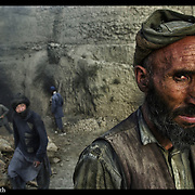 Afghanistan brickmakers look on from their makeshift factory near Kabul, Afghanisgtan, 27 Aug, 2002.