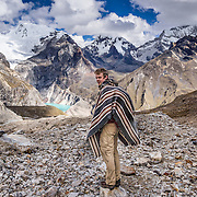 A hiker in poncho descends from Caracara Pass down into Alpamayo Valley in Huascaran National Park (UNESCO World Heritage Site), Cordillera Blanca, Andes Mountains, Peru, South America. Above the turquoise Jancarurish Lake is the pyramidal peak of Nevado Alpamayo (19,511 ft or 5947 m) in the clouds. This is day 6 of 10 days trekking around Alpamayo (starting from Vaqueria). This panorama was stitched from 2 overlapping photos.
