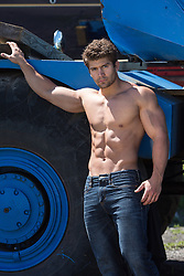 shirtless muscular man in jeans standing by a truck