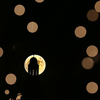 (Boston, MA - 11/25/15) A full moon is seen rising behind a building and through tree lights on Newbury Street in Boston, Wednesday, November 25, 2015. Staff photo by Angela Rowlings.