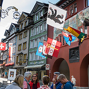 In Appenzell village, the red Rathaus (built 1560-83) houses the city hall, Appenzell Museum (in attached yellow building), tourist office and library, on Hauptgasse (Main Street), in Switzerland, Europe. The Rathaus facade mural was painted by August Schmid from Diessenhofen (1928). Appenzell Museum shows a cross section of the Swiss Canton's history and culture (1400s flags and banners, embroidery, folk art, and even historic torture instruments). Appenzell village is in Appenzell Innerrhoden, Switzerland's most traditional and smallest-population canton (second smallest by area). For licensing options, please inquire.