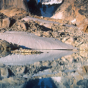 """Howser Spires (11,150 feet) reflect in a pretty tarn (mountain pond) in Bugaboo Provincial Park, south of Golden, British Columbia, Canada. The Bugaboos are a range in the Purcell Mountains, which are a subrange of the Columbia Mountains, which are west of the Rocky Mountain Trench. (Some USA maps label the """"Percell Mountains"""" where their southern limit protrudes into the states of Idaho and Montana.) The igneous Bugaboo intrusion of 135 million years ago cooled into hard crystalline granite and was scraped into spires by glaciers eroding surrounding rock dating from 600 million to 1 billion years ago. Published in the Irish Mountain Log, """"The magazine for Walkers and Climbers in Ireland"""", Summer 2008."""