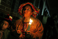 Holding candles and chanting prayers, people file down the tight streets of Chichicastenango as part of a religious procession.  La Procesion de Senor Sepultado.  An event that happens once a year.