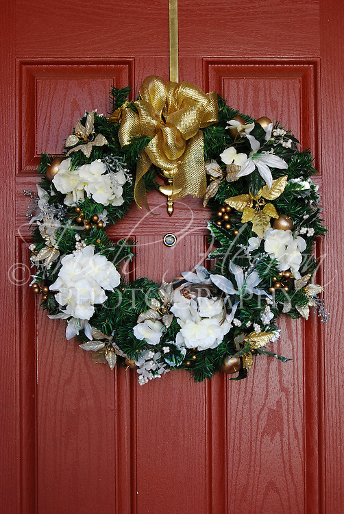 A Christmas wreath decorated in gold and white hangs on a red door.